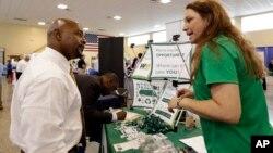 Una reclutadora da explicaciones a un desempleado. El número de solicitudes de beneficios por desempleo cayó nuevamente la semana pasada.