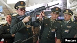 Chinese officers check rifles of ARES Defense Systems, Inc from the U.S. at the Special Operations Forces Exhibition and Conference at King Abdullah I Airbase in Amman, Jordan, May 8, 2012.