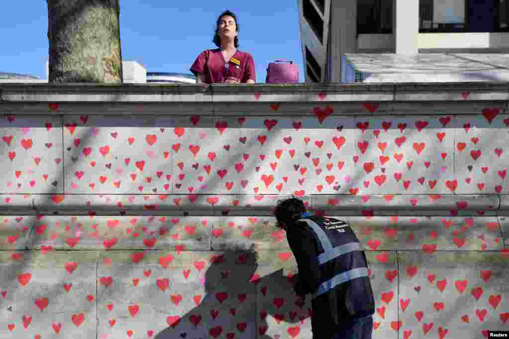 A health worker from St. Thomas' hospital stands behind a wall being painted in hearts as a memorial to all those who have died so far in the UK from COVID-19, amid the pandemic in London.