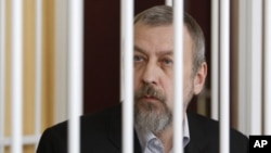 图为白俄罗斯反对派领导人、前总统候选人安德烈·桑尼科夫4月27日在笼中受审