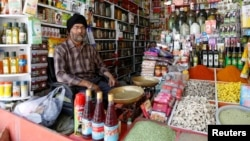 FILE - Afghan Sikh Jagtar Singh Laghmani, 50, sits at his traditional herb shop in Kabul, Afghanistan.