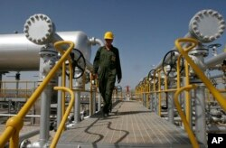 FILE - Oil technician Majid Afshari makes his way to the oil separator facilities in Iran's Azadegan oil field southwest of Tehran, April 15, 2008.
