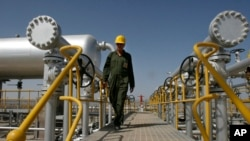 FILE - Oil technician Majid Afshari makes his way to the oil separator facilities in Iran's Azadegan oil field southwest of Tehran.