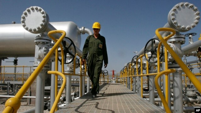 FILE - An oil technician makes his way to the oil separator facilities in Iran's Azadegan oil field southwest of Tehran, April 15, 2008.