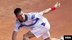 Novak Djokovic mengembalikan bola kepada Guillermo Garcia-Lopez di turnamen tenis Madrid Terbuka hari Kamis (5/5).