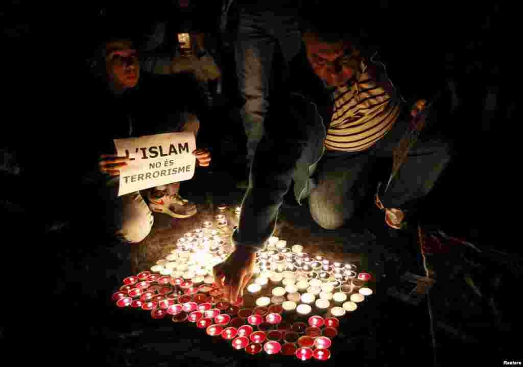 """Velas são acesas na forma da bandeira francesa em lembrança às vítimas dos ataques de Paris na PraçadeSant Jaume, em Barcelona, na Espanha. O cartaz diz """"Islã não é terrorismo""""."""