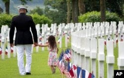 FILE - A U.S. Marine Corps soldier holds hands with a small girl as they walk among headstones of World War I dead at a Memorial Day commemoration at the Aisne-Marne American Cemetery in Belleau, France, May 27, 2018.