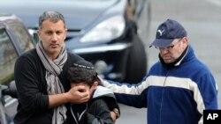 프랑스 툴루즈 시에서 발생한 유대인 학교 총격사건 현장에서 소년의 눈을 가리는 보호자.