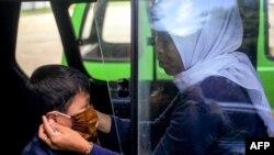 Seorang ibu memasang masker wajah untuk anaknya di dalam angkutan umum di Bogor, Jawa Barat, Rabu, 8 April 2020. (Foto: AFP)