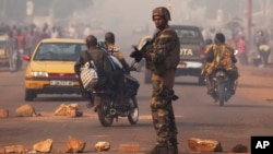 A French soldier waves through traffic as he mans a roadblock in the Miskine neighborhood of Bangui, Central African Republic, Jan. 6, 2014.
