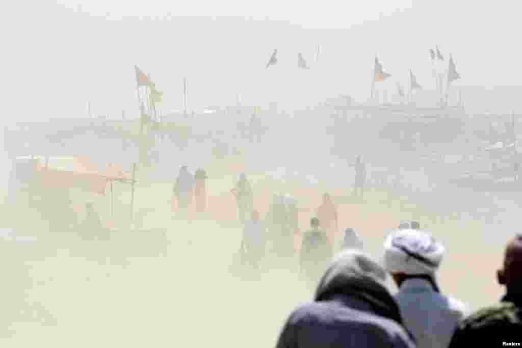 មនុស្សម្នាដើរកាត់ព្យុះធូលីដីនៅលើច្រាំងទន្លេ Ganga នៅក្នុងក្រុង Allahabad ប្រទេសឥណ្ឌា។