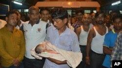 Seorang pria memegang anaknya yang meninggal di luar RS Perguruan Tinggi Kedokteran Baba Raghav Das di Gorakhpur, India (11/8).