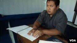Taufik Windu Asmoro, seorang penyandang difabel, tengah membaca Al-Qu'ran Braille di Mangkuyudan, Solo (16/7). Para penyandang difabel di kota ini mengisi kegiatan di bulan Ramadan dengan mengikiti TPA Al-Qur'an Braille.