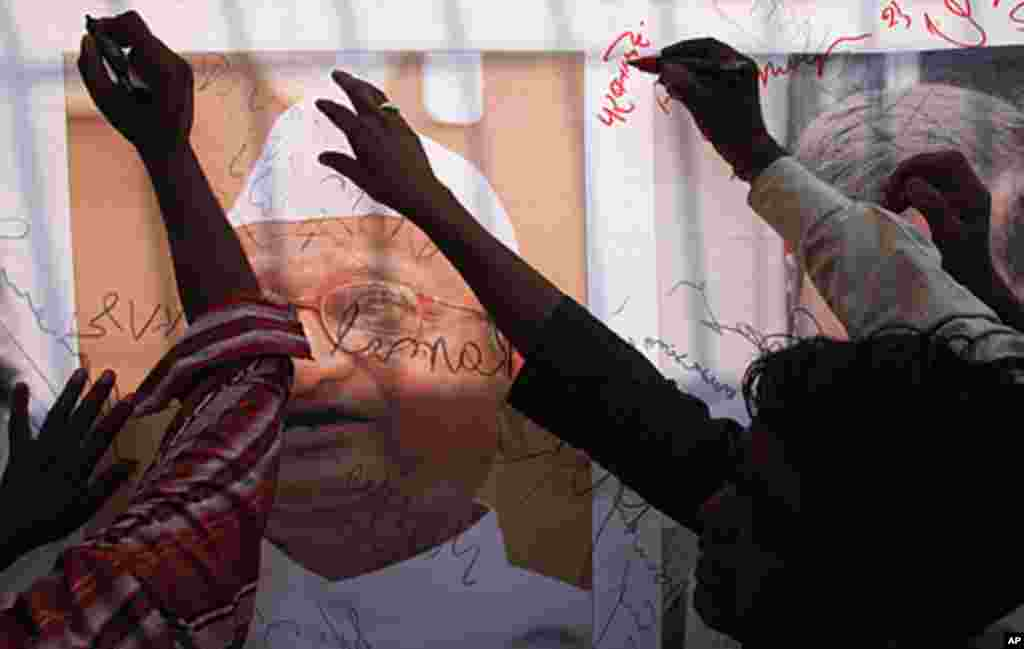Supporters of veteran Indian social activist Anna Hazare sign a banner with a portrait of Hazare outside the Tihar jail in New Delhi August 17, 2011. (Reuters)