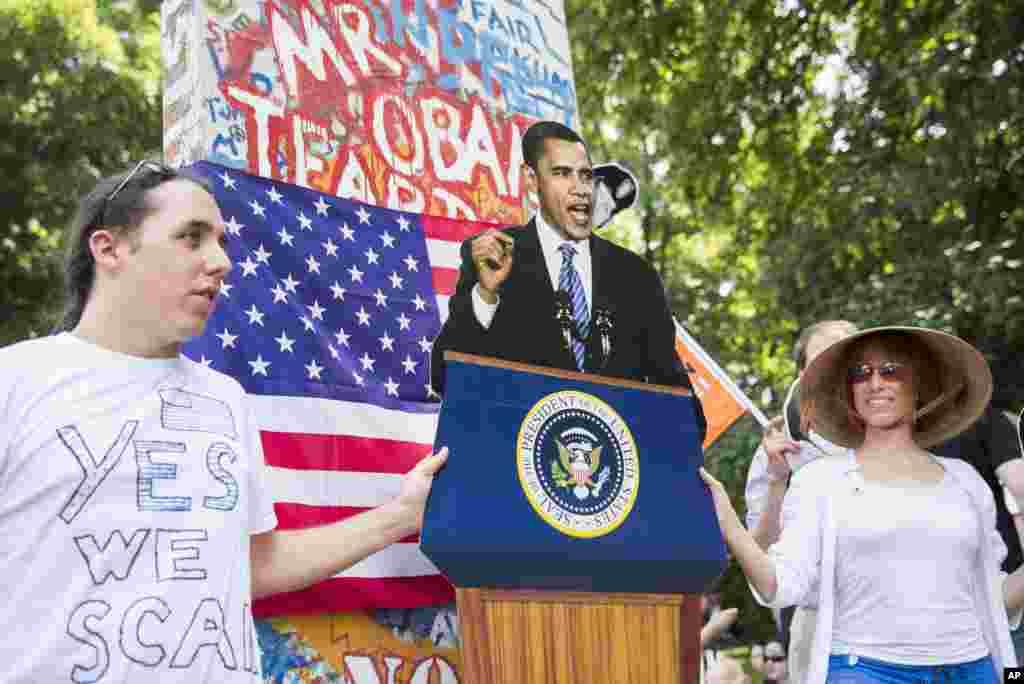 """Etiraz nümayişçiləri keçmiş Berlin divarının bir hissəsinin kopyası üzərində """"Bu divarı sökün, cənab Obama"""" yazılmış plakat turub."""
