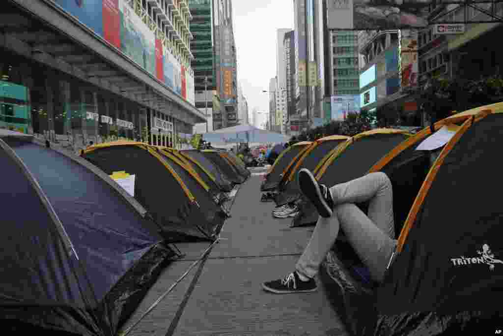 A protester rests in his tent near a main road in the Mongkok district, Hong Kong, Oct. 15, 2014.