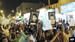 قاطف، سعودی عرب میں شیعہ مظاہرین سعودی جھنڈے اور سیاسی قیدیوں کے پورٹریٹ اٹھائے ہوئے مظاہرہ کررہے ہیں۔