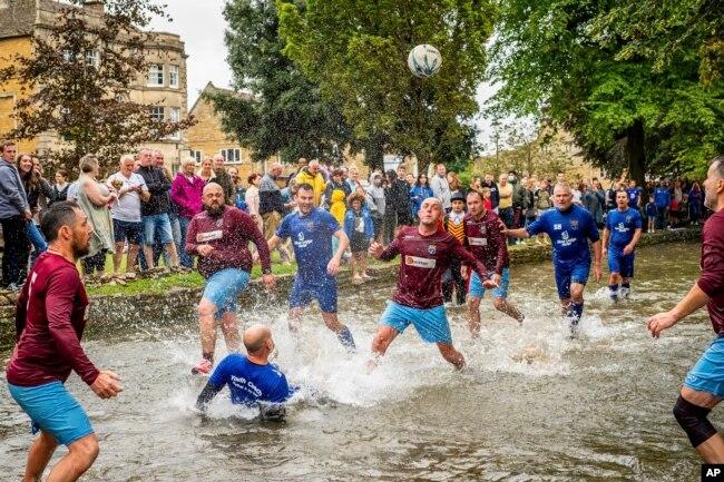 Para pesepakbola berebut bola di Sungai Windrush dalam pertandingan sepak bola sungai tradisional tahunan di desa Cotswolds, Bourton-in-the-Water, Inggris, Senin, 30 Agustus 2021. (Ben Birchall/PA via AP)