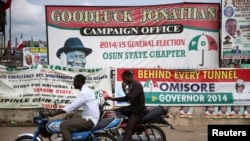 FILE - Men ride past motorcycles in front of a Peoples Democratic Party office at the Osun state governorship election in Osogbo, southwest Nigeria, Aug. 9, 2014.
