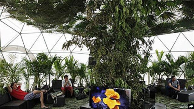 People sit in an exhibit on climate change during the United Nations Climate Change Conference in Cancun, Mexico, Dec. 1, 2010