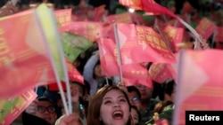 在台北民进党总部外的蔡英文总统的支持者举旗欢呼。(2020年1月11日)