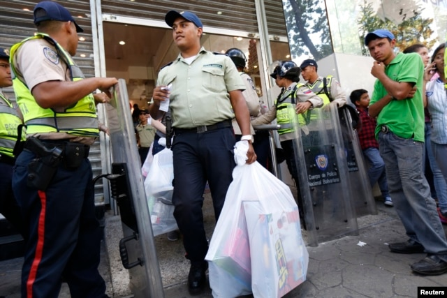 A police officer carries his shopping out of a department store, which was forced by the government to cut prices by at least 50 percent on all merchandise after an inspection, in Caracas Nov. 15, 2013.