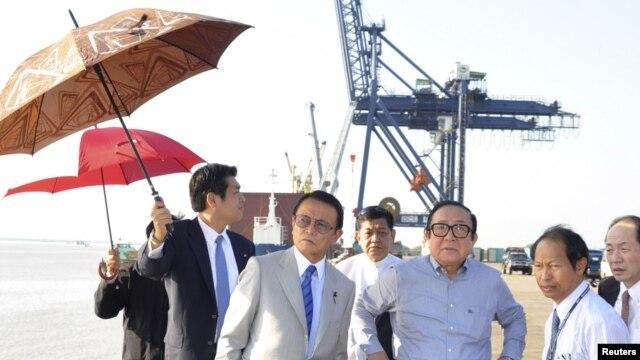 Wakil Perdana Menteri merangkap Menteri Keuangan Jepang, Taro Aso (tengah) didampingi Ketua Asosiasi Jepang-Burma, Hideo Watanabe (tengah, kanan( mengunjungi sebuah kawasan industri di Thilawa, dekat Yangon (Rangun), 4 Januari 2013. (REUTERS/Pool)