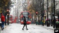 Seorang perempuan berjalan menyeberangi Jalan Oxford di London yang dipenuhi para pengunjung, di tengah hujan salju, Minggu, 10 Desember 2017. (AP Photo/Alastair Grant)