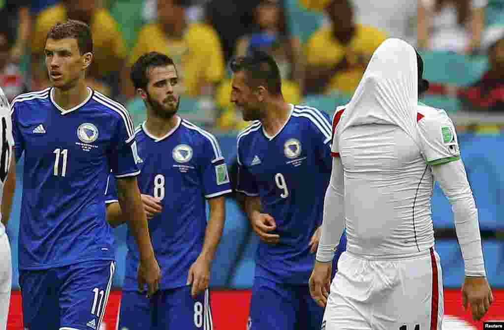 Iranian Andranik Teymourian covers his face as Bosnians Edin Dzeko, Miralem Pjanic and Vedad Ibisevic celebrate their team's second goal at the Fonte Nova arena, in Salvador, June 25, 2014.