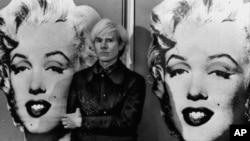 지난 1971년 5월 영국 런던에서 앤디 워홀이 여배우 메릴린 먼로 그림을 배경으로 포즈를 취하고 있다.