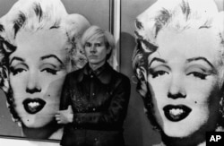 America's pop art painter and filmmaker, Andy Warhol, stands in front of his double portrait of the late Hollywood film star, Marilyn Monroe, at The Tate Gallery in London, February 15, 1971, at a press preview of his exhibition. (AP Photo)
