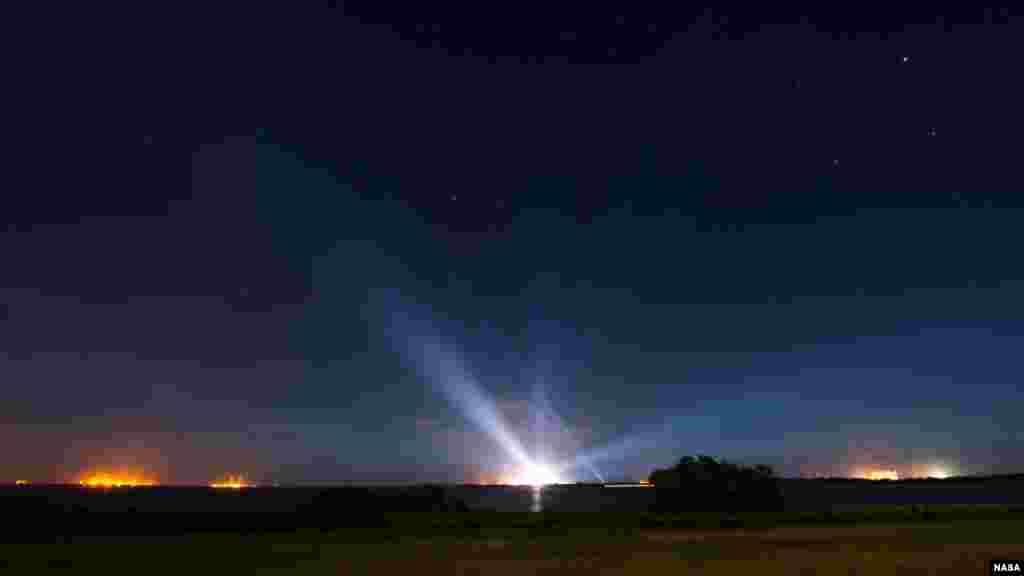 Le vaisseau spatial Orion de la NASA, accroché sur la fusée Launch Alliance Delta IV Heavy, est aperçu au loin, illuminé, dans cette photographie d'exposition prises tôt le jeudi 4 décembre 2014, au complexe de lancement spatial de Base de lancement de Cap Canaveral.