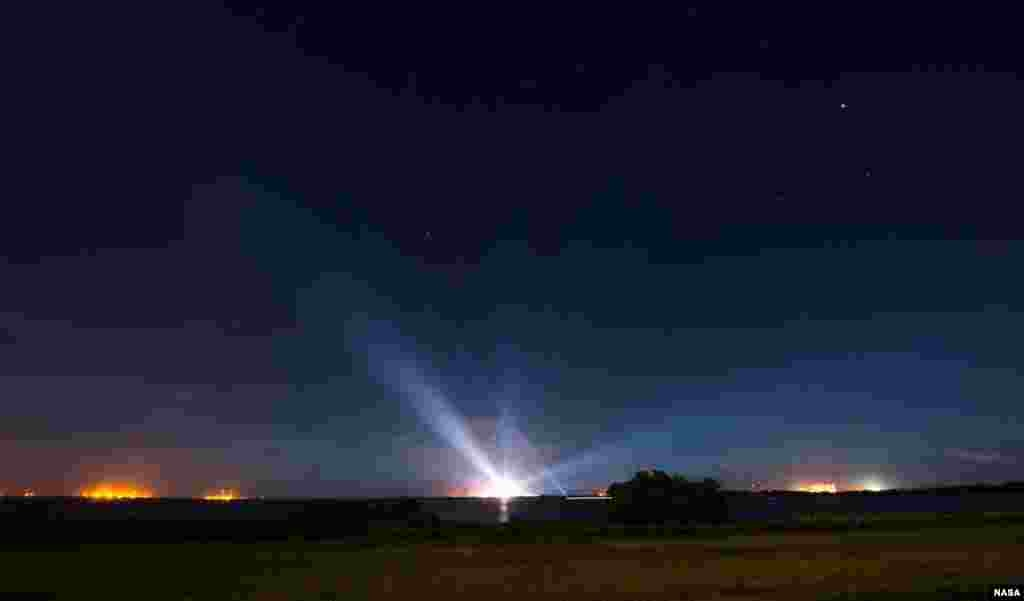 A United Launch Alliance Delta IV Heavy rocket with NASA's Orion spacecraft mounted atop is seen illuminated in the distance at Cape Canaveral Air Force Station's Space Launch Complex 37, Florida.