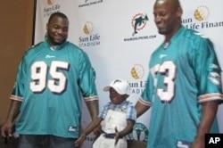 Miami Dolphins Jason Ferguson, left, and Reggie Torbor with Haiti earthquake survivor Snyder, 3 in Little Haiti, 7 Apr 2010