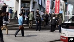 FILE - Plainclothes security personnel film as they prepare to load detained worshipers onto a waiting bus near an unregistered house church in Beijing, China, April 10, 2011.