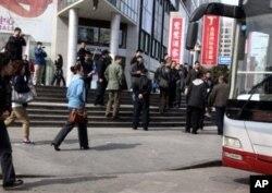 Nhân viên an ninh mặc thường phục quay phim khi tập trung để bắt giữ những tín đồ lên xe buýt gần một tòa nhà. Những người đứng đầu nhà thờ chưa được đăng ký Shouwang đã kêu gọi giáo dân tụ tập tại Bắc Kinh, Trung Quốc, ngày 10 tháng 2 năm 2011.
