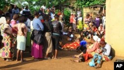 Family members and onlookers mourn over the bodies of civilians killed by The Allied Democratic Forces rebels in Beni, Eastern Congo, Oct 5, 2018.