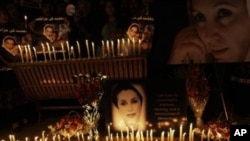 Posters of Pakistan's slain leader Benazir Bhutto and candles are held by her supporters at a ceremony to mark the third anniversary of her death, in Islamabad, Pakistan, 27 Dec 2010.