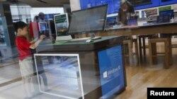 一名儿童站在纽约一家微软商店的展示电脑视窗10操作系统的展示台前。(2015年7月29日)