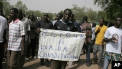 """ຜູ້ຊາຍຄົນນຶ່ງຖືປ້າຍອ່ານວ່າ """"ຈົ່ງນໍາເອົາລັດຖະທໍາມະນູນຄືນມາປະຕິບັດ"""" ໃນການປະທ້ວງ ຕໍ່ຕ້ານການເຮັດລັດ ຖະປະຫານຂອງທະຫານ ທີ່ນະຄອນ Bamako ປະເທດ Mali ໃນວັນຈັນທີ 26 ເດືອນມີນາ 2012."""