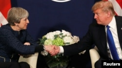 FILE - U.S. President Donald Trump shakes hands with British Prime Minister Theresa May during the World Economic Forum annual meeting in Davos, Switzerland, Jan. 25, 2018.