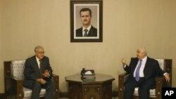 Utusan PBB Lakhdar Brahimi (kiri) saat bertemu dengan Perdana Menteri Suriah Walid Moallem. (AP/Muzaffar Salman)
