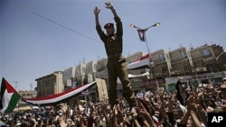 A Yemeni army officer is lifted by anti-government protesters gestures as he joins them in a demonstration demanding the resignation of President Ali Abdullah Saleh, in Sana'a, March 24, 2011