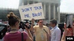 """Para penentang Obamacare melakukan unjuk rasa di depan Mahkamah Agung AS dengan tulisan: """"Don't Tax Me Bro!"""" (28/6)."""