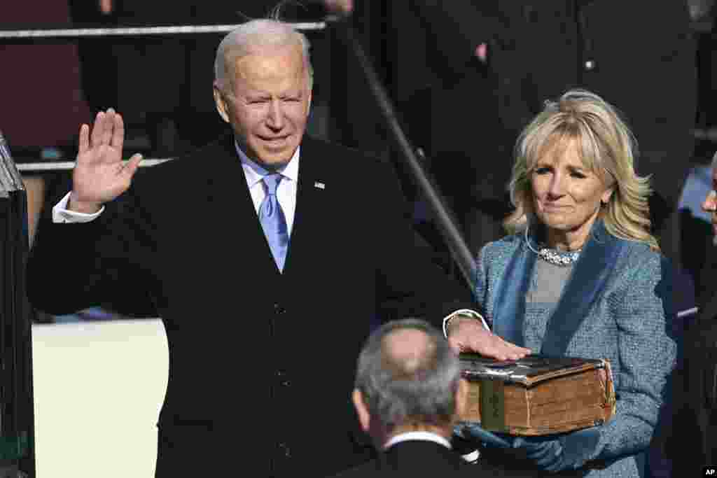 Joe Biden is sworn in as the 46th president of the United States by Chief Justice John Roberts as Jill Biden holds the Bible during the inauguration at the Capitol in Washington, D.C.