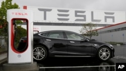 FILE - A Tesla car is parked at a charging station outside the Tesla factory in Fremont, California, May 14, 2015.