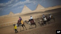 Tourists ride camels near the pyramids, in Giza, Egypt, January 31, 2011. The pyramids are closed to tourists.