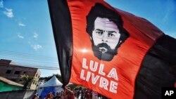 Un partidario del ex presidente brasileño, Luiz Inácio Lula da Silva, alza una pancarta decorada con una imagen que representa a da Silva, frente al Departamento de Policía Federal, donde está cumpliendo condena en la cárcel.