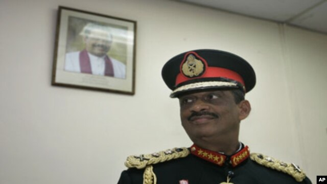 A portrait of Sri Lankan president Mahinda Rajapaksa is seen on the wall as Sri Lankan military chief General Sarath Fonseka looks on at the military headquarters after his retirement in Colombo, Sri Lanka, Monday, 16 Nov 2009