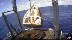 In this March 8, 2019 file image taken from video made available by NASA, the SpaceX Crew Dragon capsule is hoisted onto a ship in the Atlantic Ocean off the Florida coast after it returned from a mission to the International Space Station.